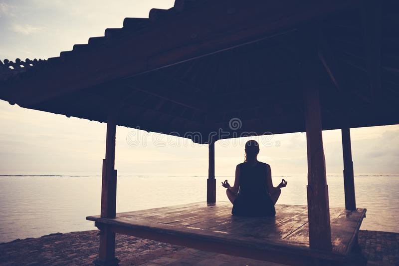 Silhouette of woman doing yoga practice in sun shelter near ocean royalty free stock photos