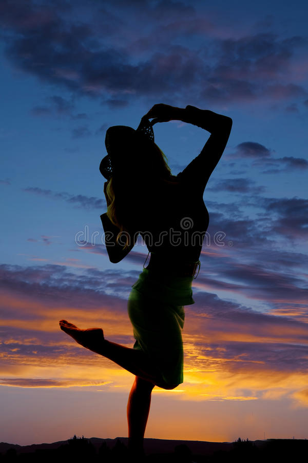 Silhouette of a woman in dress hand on hat kick up leg royalty free stock photography
