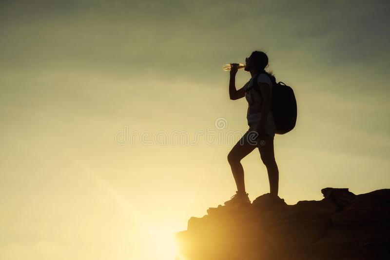 Silhouette woman drink water to cliff in sunset stock photography