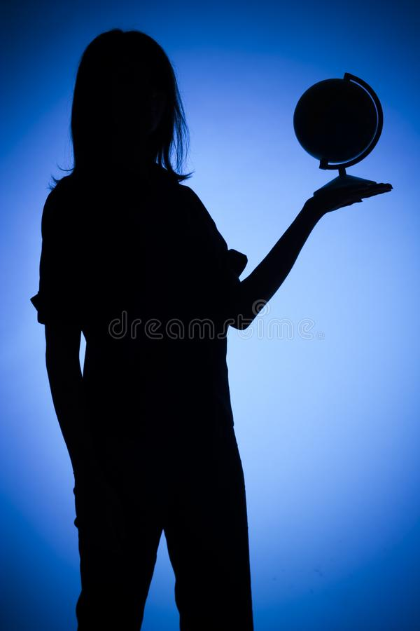 Silhouette of woman with globe stock photography