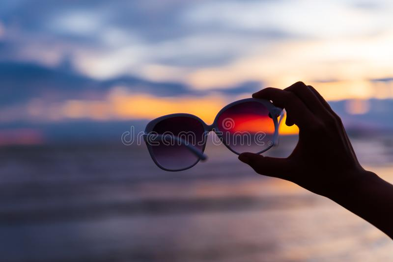 Silhouette woman hand holding sunglasses over sea and Sandy. Beach in background during sunset for summer holiday and vacation concept royalty free stock photos