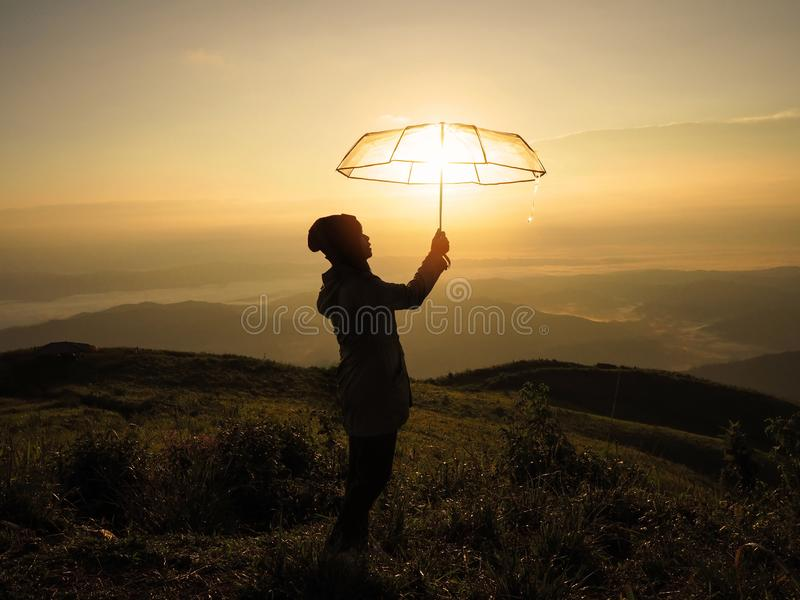 Silhouette woman hand holding umbrella on mountain at sunrise royalty free stock photography