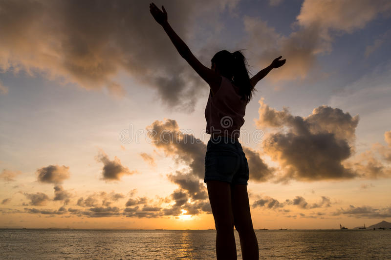Silhouette of woman hand up under sunset. Asian young woman stock images