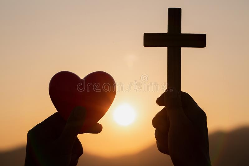Silhouette of woman hands praying with cross and holding a red heart ball in nature sunrise background, Crucifix, Symbol of stock photography