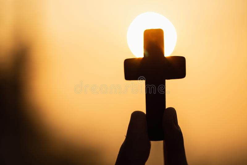 Silhouette of woman hands praying with cross in nature sunrise background, Crucifix, Symbol of Faith. Christian life crisis. Prayer to god stock photography