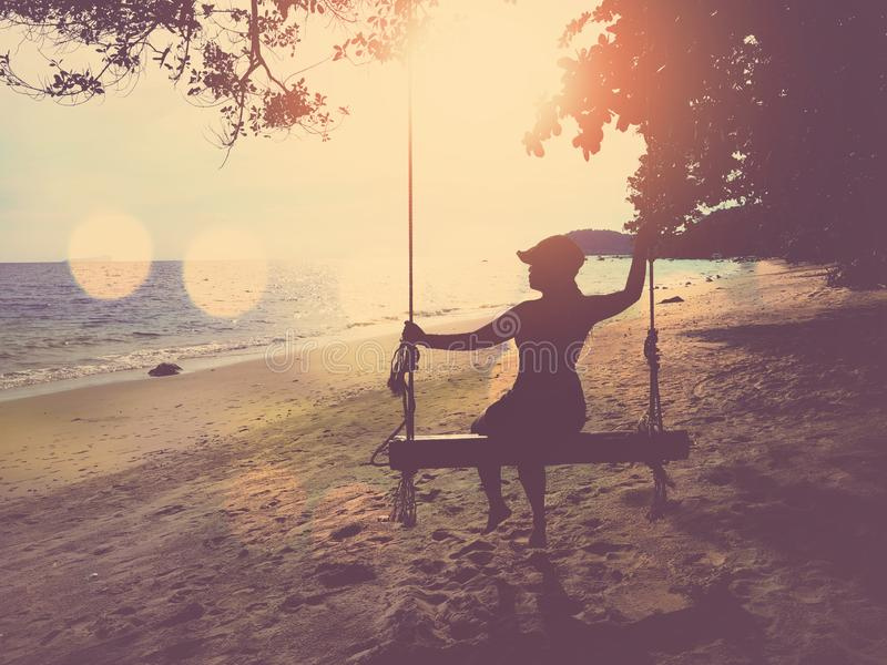 Silhouette woman with hat sitting on wooden swing at sunset beach background stock images