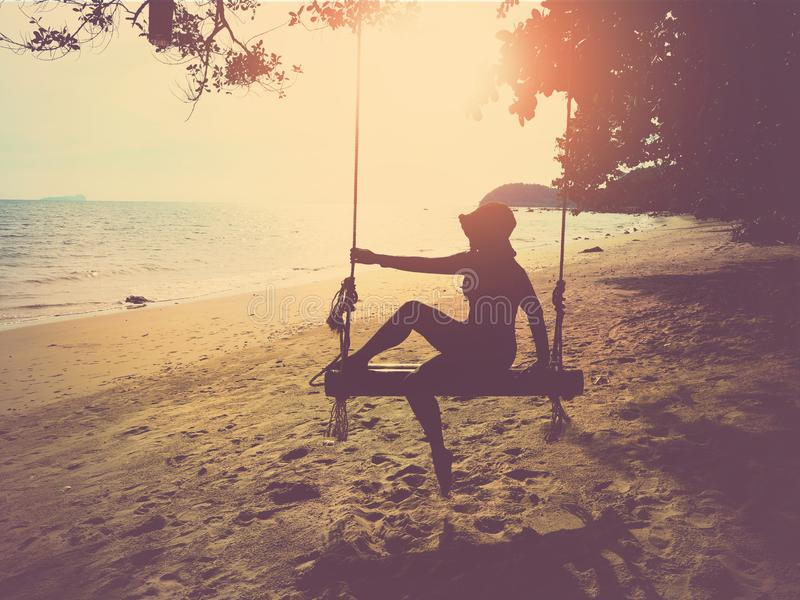 Silhouette woman with hat sitting on wooden swing at sunset beach background royalty free stock photography