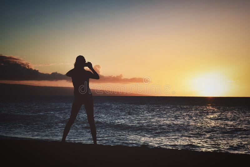 Silhouette of Woman Holding Camera Near Seashore during Golden Hour stock photo