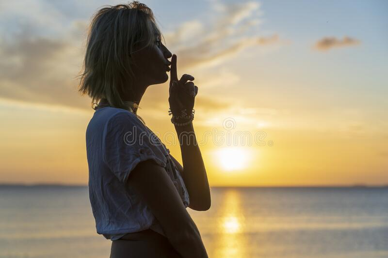 Silhouette of woman holding finger on her lips against a beautiful sunset near sea waves on the beach, closeup. Girl with finger. Silhouette of woman holding royalty free stock images