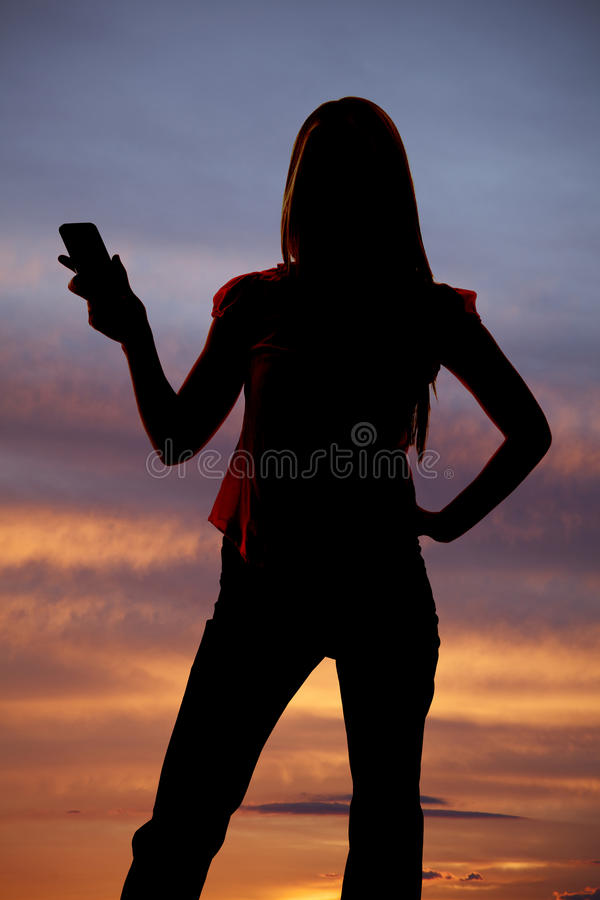 Silhouette of woman holding out cell phone sunset. royalty free stock photos