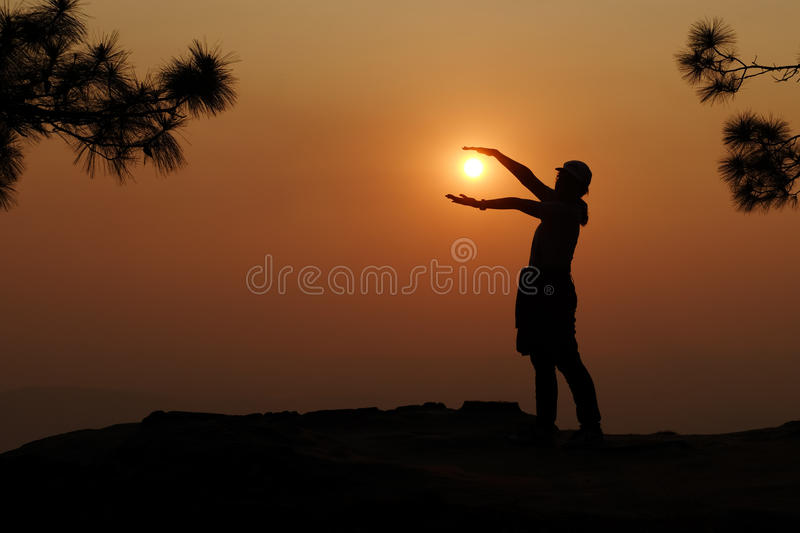 Silhouette of woman holding the sun stock image