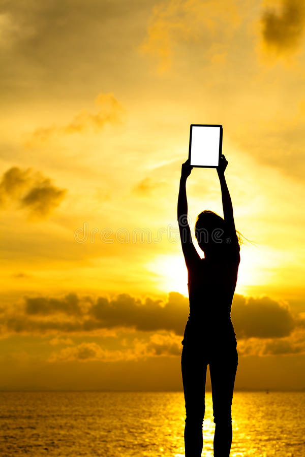 Download Silhouette Of Woman Holding Tablet Computer At Sunset Stock Photo - Image: 31974854