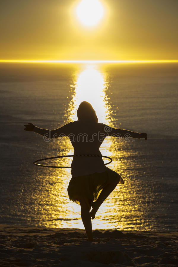 Silhouette of woman hoola hooping. A Silhouette of a woman balancing on one foot while hoola hooping facing the sun royalty free stock photos