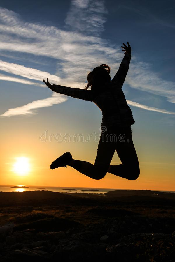 Silhouette of a woman jumping stock photos