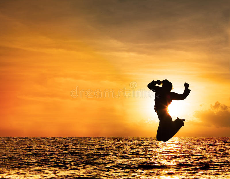 Silhouette of woman jumping at sunset. Silhouette of a beautiful jumping woman against orange sky at sunset royalty free stock photos