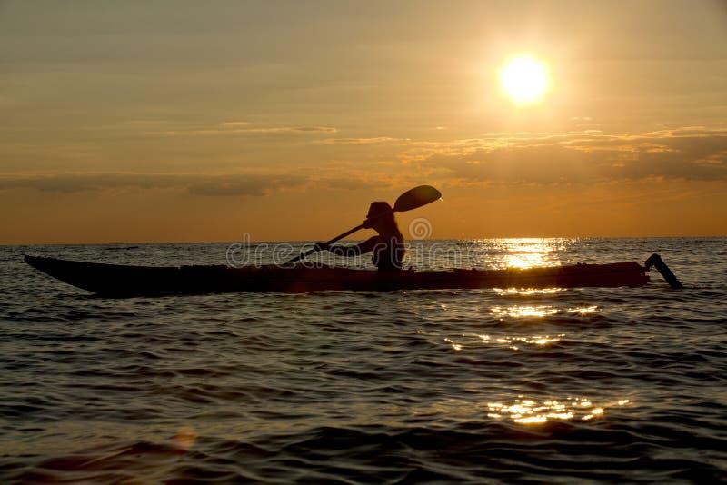 Silhouette of woman kayaking royalty free stock image