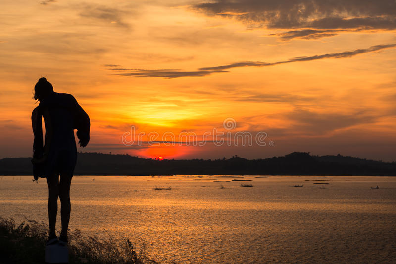 Silhouette of woman at lake ,sunrise background. Silhouette of free woman enjoying freedom feeling happy at sunset. Serene relaxing woman in pure happiness stock images
