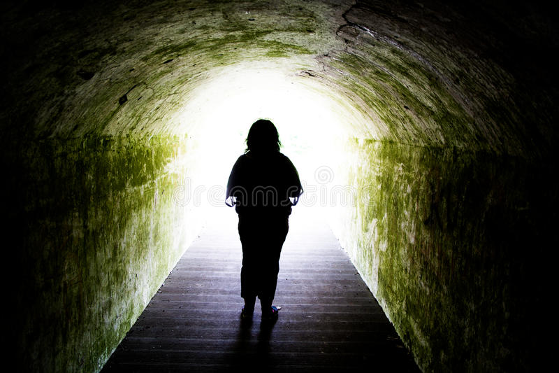 Silhouette of woman in light at end of tunnel royalty free stock photos