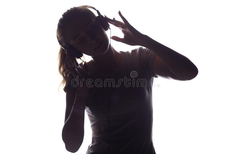 Silhouette of woman listening to music in headphones stock images