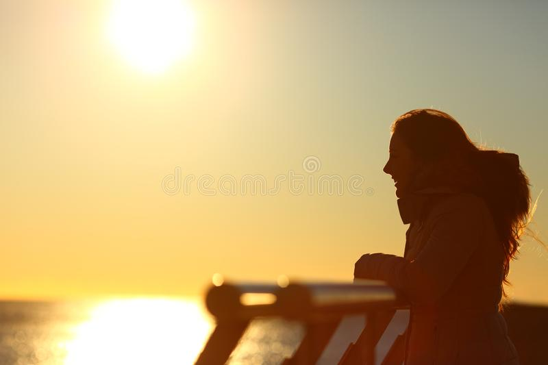 Silhouette of a woman looking at horizon at sunset. Side view portrait of a silhouette of a woman looking at horizon at sunset on a bridge over the sea stock photo