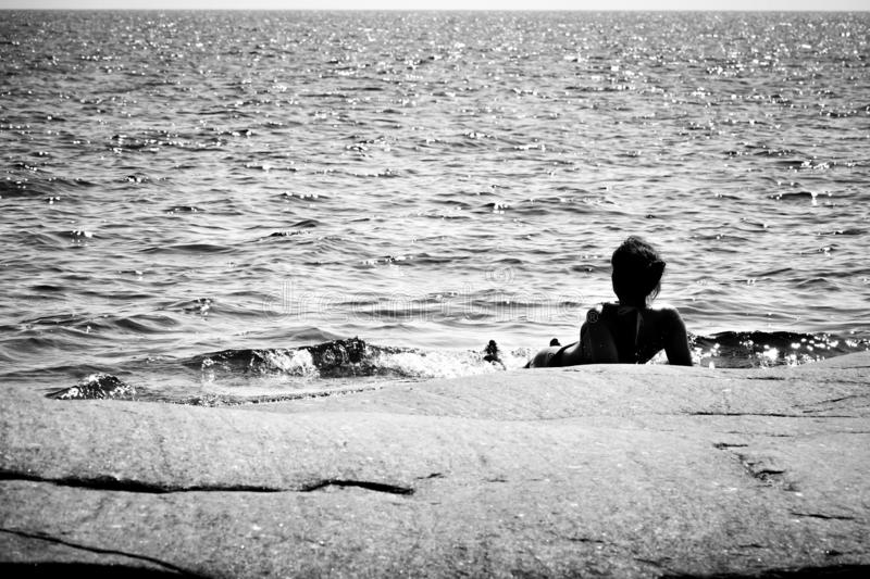 Silhouette of woman lying on a rock in the ocean. stock images