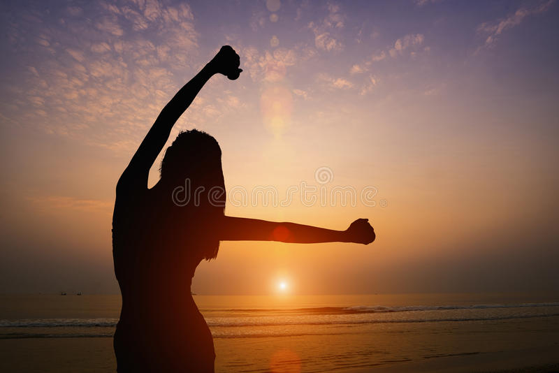 Silhouette of woman making yoga on the beach with sunset background royalty free stock images
