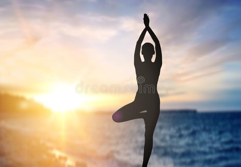 Silhouette of woman making yoga over sea sunset royalty free stock photography