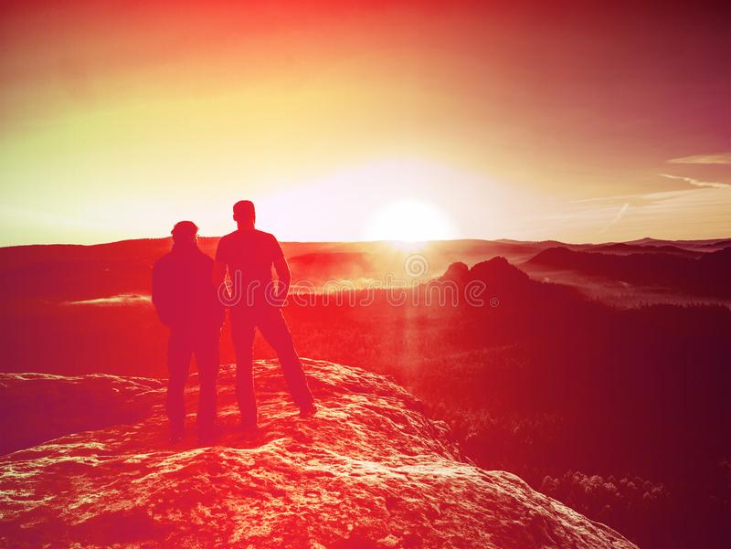 Silhouette woman and man at sunset on top mountain royalty free stock image