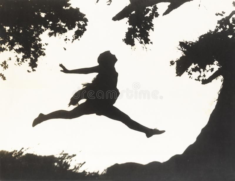 Silhouette of a woman in mid-air jumping between two trees stock photography