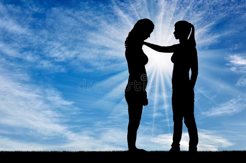 A silhouette of a woman morally supports another woman royalty free stock images