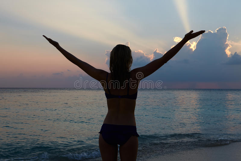 Silhouette Of Woman With Outstretched Arms On Beach stock image