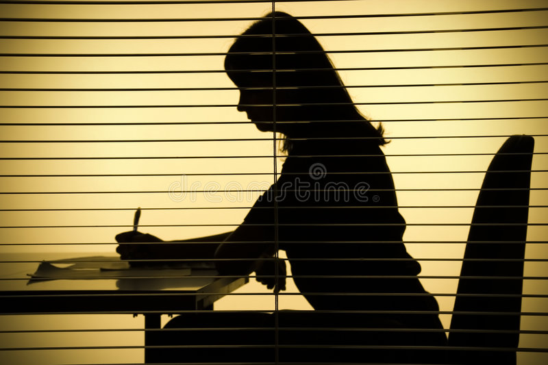 Silhouette of woman with papers (view through the blind) royalty free stock photo