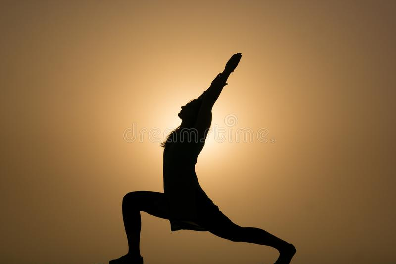 Silhouette of woman performing yoga in the sunset. Silhouette of a woman performing the crescent moon Hatha yoga posture in the golden light of the setting sun stock photo