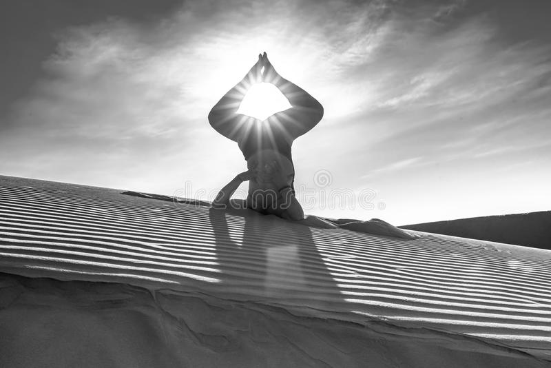 Silhouette woman performing yoga exercises workout. On the sand dunes in the morning when the sun higher welcomes new day beautiful royalty free stock images