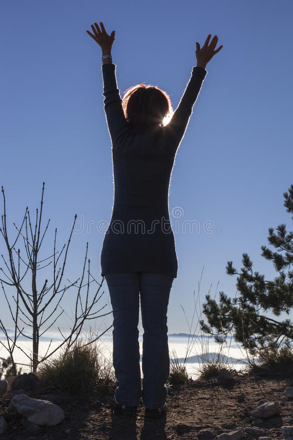 Silhouette of a woman performing Yoga with the sun shining behind her. Silhouette of a woman meditating and performing Yoga, with the sun shining behind her royalty free stock images