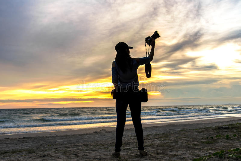 Silhouette of a woman photographer standing in the beach sunset stock photo