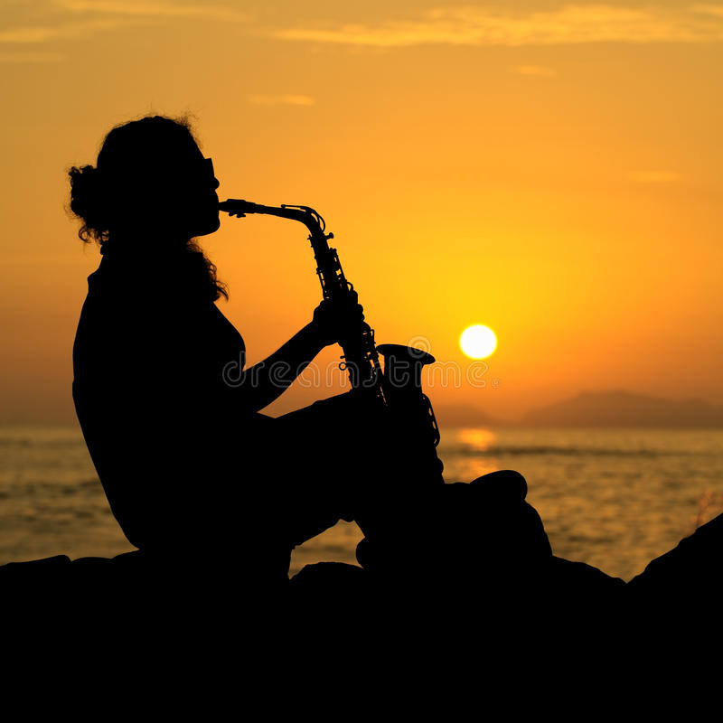 Silhouette of a Woman Playing the Saxophone stock photos