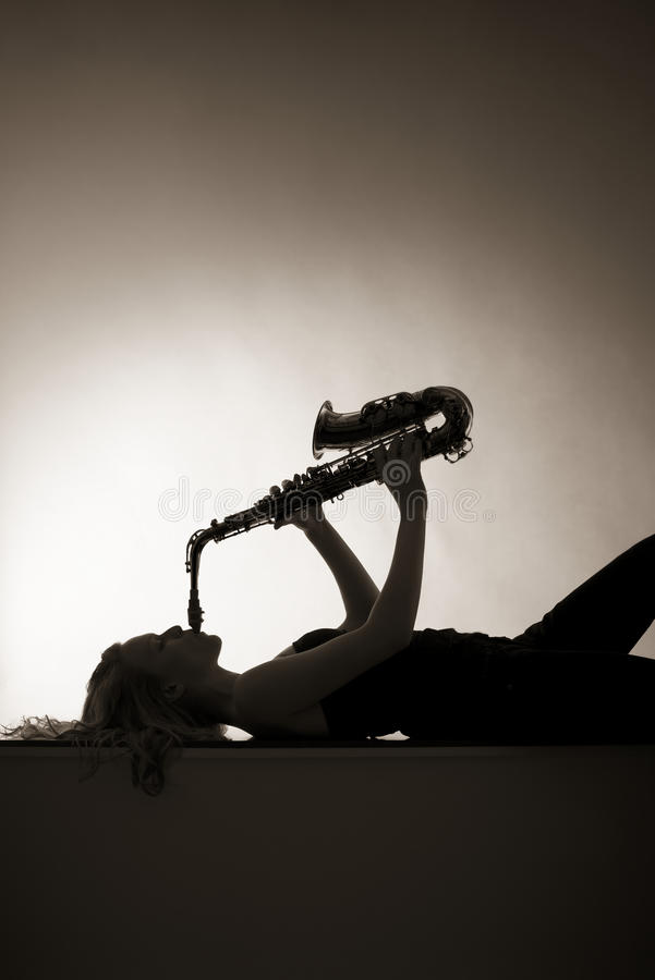 Silhouette of woman playing saxophone, sepia toned stock photography