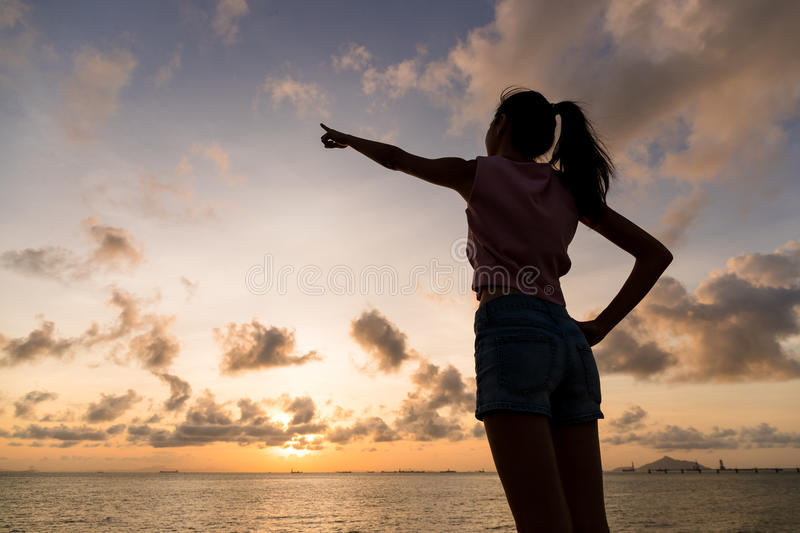 Silhouette of woman pointing finger far way. Asian young woman royalty free stock photography