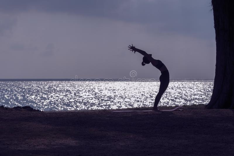 Silhouette of woman practicing yoga on the beach stock photography