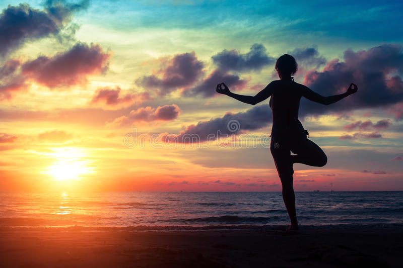 Silhouette woman practicing yoga on the beach at sunset. stock photography