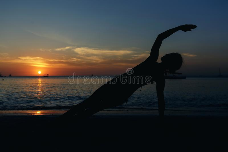 Silhouette of woman practicing yoga on ocean coast at sunset royalty free stock photography