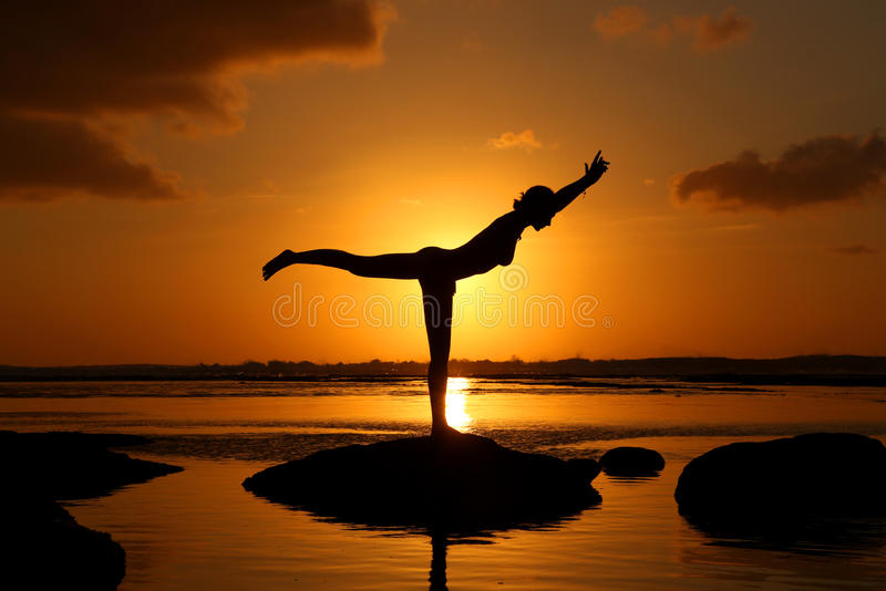 Silhouette of woman practicing yoga stock photography
