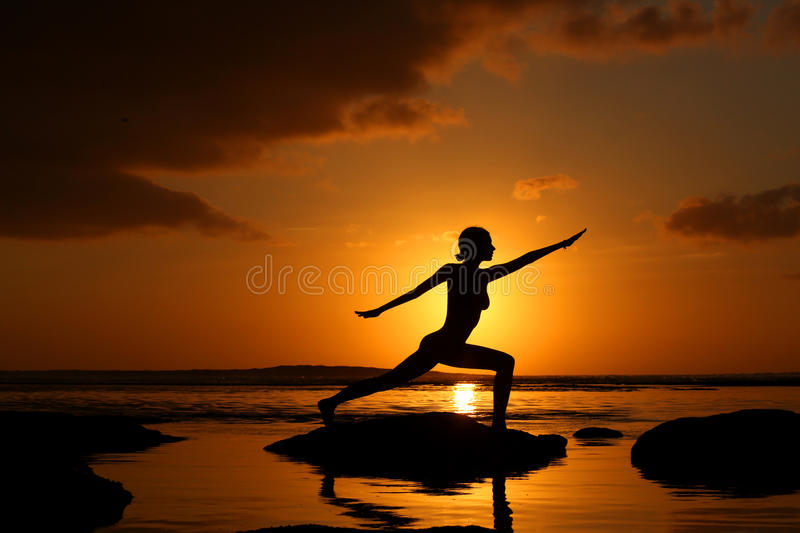 Silhouette of woman practicing yoga royalty free stock image
