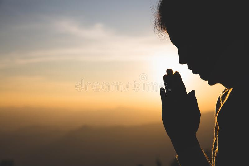 Silhouette of a woman  Praying hands with faith in religion and belief in God On the morning sunrise background.  Namaste or royalty free stock photo