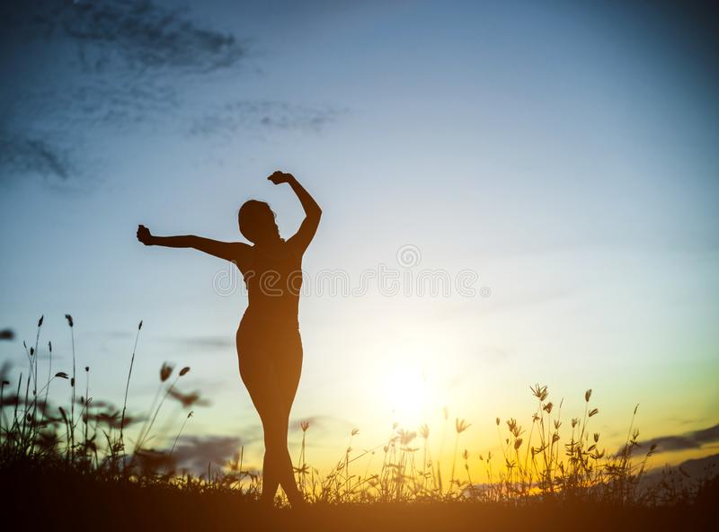 Silhouette of woman praying over beautiful sky background. Silhouette of free cheering woman hiker open arms at mountain peak beautiful sky background stock photography