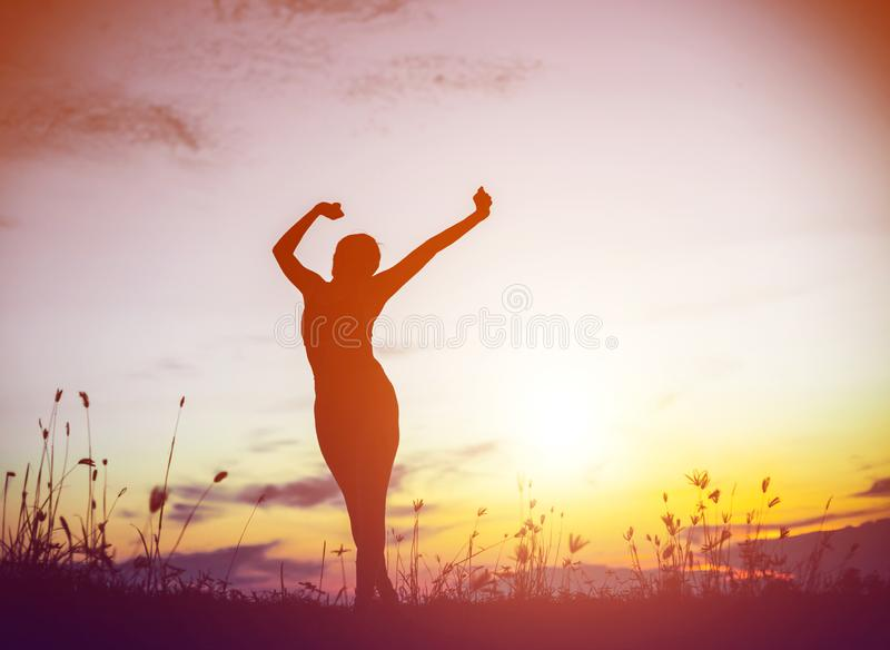Silhouette of woman praying over beautiful sky background. Silhouette of free cheering woman hiker open arms at mountain peak beautiful sky background stock images