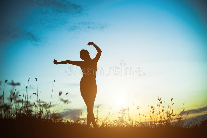 Silhouette of woman praying over beautiful sky background. Silhouette of free cheering woman hiker open arms at mountain peak beautiful sky background royalty free stock photography
