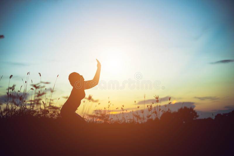 Silhouette of woman praying over beautiful sky background. Silhouette of free cheering woman hiker open arms at mountain peak beautiful sky background royalty free stock photos