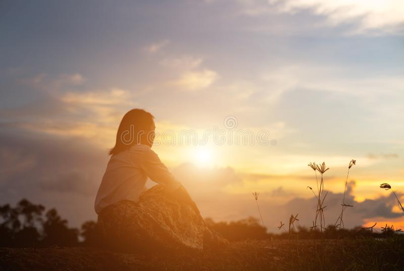 Silhouette of woman praying over beautiful sky background. Silhouette of free cheering woman hiker open arms at mountain peak beautiful sky background royalty free stock images